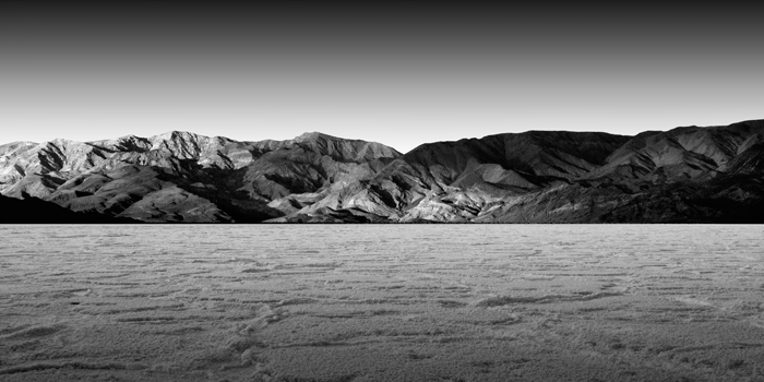 """badwater"" © kevin saint grey, my friend Jeff and I visited Death Valley to photograph. I found it really difficult to get anything I really liked out of that trip and I ended up sitting on most of my images for over a year while Jeff sent occasional emails asking me if I had processed anything yet. I ended up with very few usable images but I really liked the simplicity of this image taken in Badwater. On the day before this was taken, we were in the same spot photographing during sunset as a lightning storm erupted around us. We were completely in awe as lightning crashed and we were running around trying to take as many images as we could. It started to get completely black as forty to fifty miles per hour winds gusted around us and both my cameras fell over while attached on their tripods. I still have some salt crusted onto one of my cameras from that day."