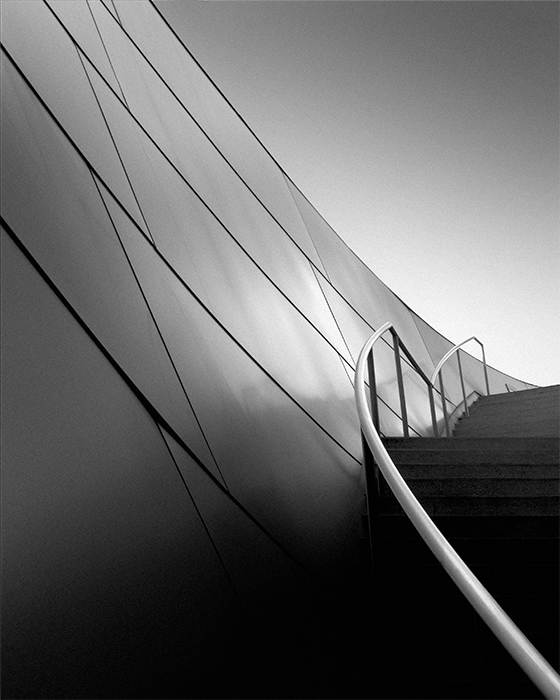"""harmonic III"" ©kevin saint grey For the past few years, I have been working (on and off) on a series of the Disney Concert Hall. The building, notable for the Gehry design lacks in symmetry and has some unusual curves that makes composing an image difficult for me. This is the first image of this subject where I felt the elements really worked together -- the opposing lines of the handrail and the wall give the image tension without being disjointed while the horizontal lines in the staircase give the foundation."