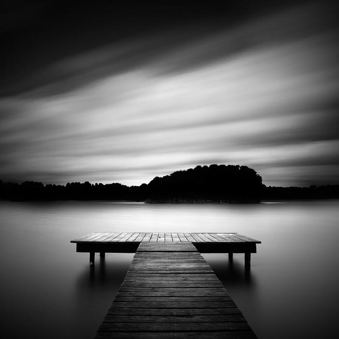 """I slowed down and looked over the lake"" (c) Bernd Walz At dusk at one of the innumerable lakes north of Berlin. I found this peaceful location, made a long exposure and processed the image in a way ( I forgot the details) that it had this light reflection between the jetty and the opposite shore. I attempted an absolutely peaceful atmosphere, an atmospheric, silent image that reflected my own mood at this late Sunday."