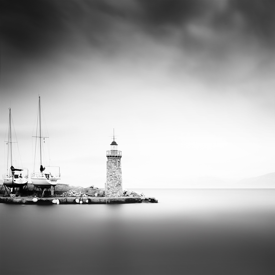 """Misty scapes_IX"" (c) Vassilis Tangoulis A misty day in Egion, a town close to Patra where there is this perfet lighthouse. Was lucky not having in fron t of it distracting small boats and also a mist in the background. I worked mainly to emphasize the influence of the mist in the background and the light tones in the sea."
