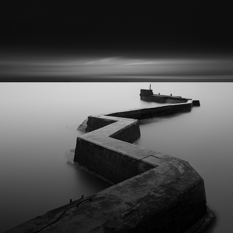 """Breakwater"" (C) Gavin Dunbar This was my first and so far only visit to this location to shoot this very photogenic breakwater, and one of those rare days when everything fell into place - the tide was right, the clouds were perfect as was the light. I remember it being extremely windy with a large swell constantly smashing up against the breakwater, so it really shows off the power of longer exposures to change the feel of an image compared to what you actually see at the time. Processing wise I always use Adobe Lightroom to make all my basic adjustments to the RAW files such as slight sharpening, fixing wonky horizons, or any exposure or contrast adjustments etc. The image is then loaded into Silver Efex Pro 2 and converted to black and white, and then into Photoshop CS5. I usually process the original RAW file a couple of times in Silver Efex Pro to give me an overexposed version and an underexposed or neutral version, then I'll blend various parts from each to get the look I am after for the final image."
