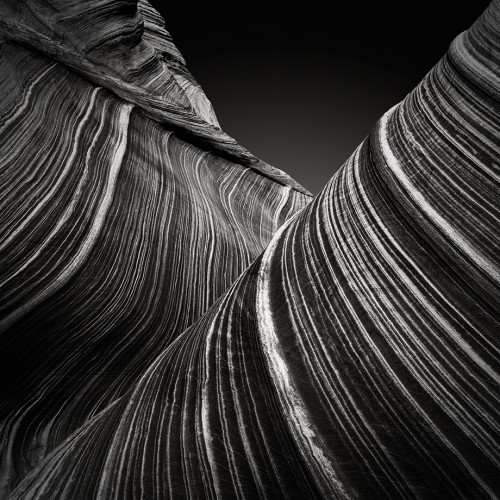 Sensual Curves (c) Jan Bell: This image is about texture and design – two of my favorites. Typically I do not photograph on bright sunny days. But since I had hiked for a couple of hours to reach the location with about 28 pounds on my back, I was prepared to make a full day of it. Fortunately the rock in this area was not reflecting any specular highlights (as wet rock does). So I set out to find interesting compositions and enjoy an afternoon of shooting. Going against all convention, this composition divides the frame diagonally from corner to corner; but I feel that it works. There are so many flowing lines that counter the harsh diagonal line. While many photographers think in terms of rules, I do not, although I'm sure that 'rules' were implanted in my brain during four years of design training. Regardless, I look at a composition from an aesthetic point of view. I ask myself whether it feels good to me on a gut level? Is it free of unnecessary clutter, etc.? I added a slight vignette to draw the eye into the frame. I darkened down the sky, while masking the rock, so as not to distract from its flowing lines. I love their play of light against dark. The lines lead the viewer's eye into, and through, the composition. There is no scale or any point of reference for that matter. Therefore the photo is simply a study of texture, form, the play of light, as well as composition.